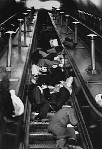 Люди спят на эскалаторе в метро.