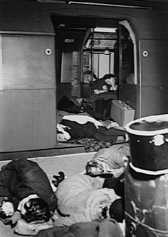 Люди спят в вагоне метро.