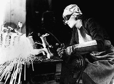 Женщина, квалифицированный токарь, на военном заводе.