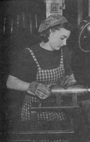 Женщина-токарь обтачивает нос снаряда.