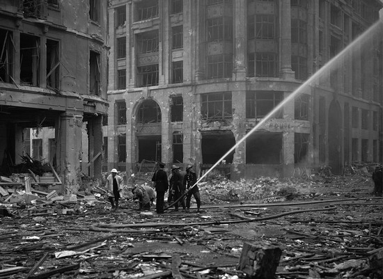 Пожарные тушат разрушенное здание недалеко от Лондонского моста в Сити, Лондон, после серии воздушных налетов, 9 сентября 1940 года. (AP Photo)