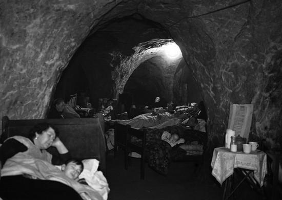 Сотни человек, оставшихся без крыши над головой в результате бомбардировок, ночуют в пещерах в городе Гастингс на юго-востоке Англии. Определенные участки пещер были отведены для и отдыха и развлечений. Некоторые люди перенесли сюда свою мебель и кровати. Фото было сделано 12 декабря 1940 года. (AP Photo)