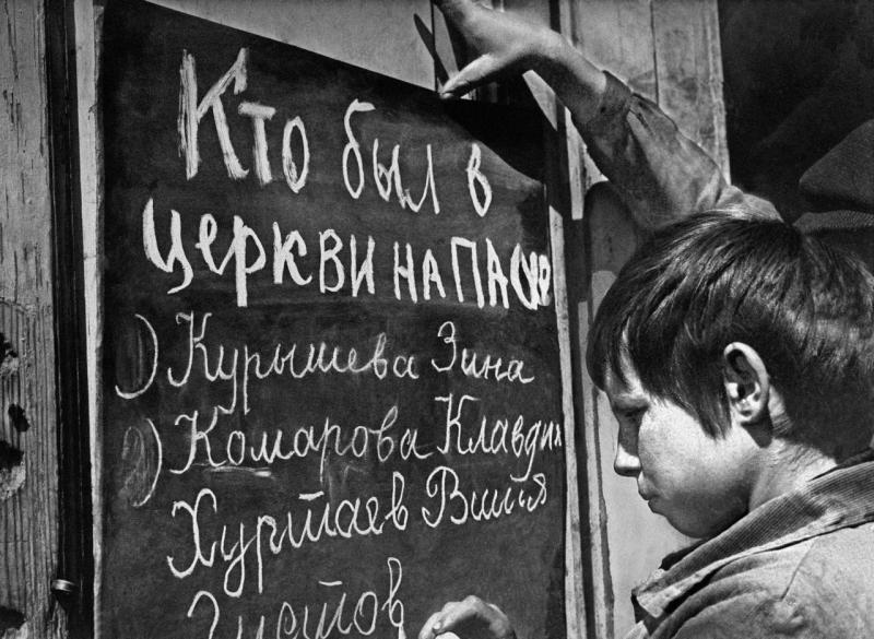 Школьники-безбожники наносят на доску фамилий людей, пришедших в церковь на Пасху. Саратовская область, 1928 год. ТАСС