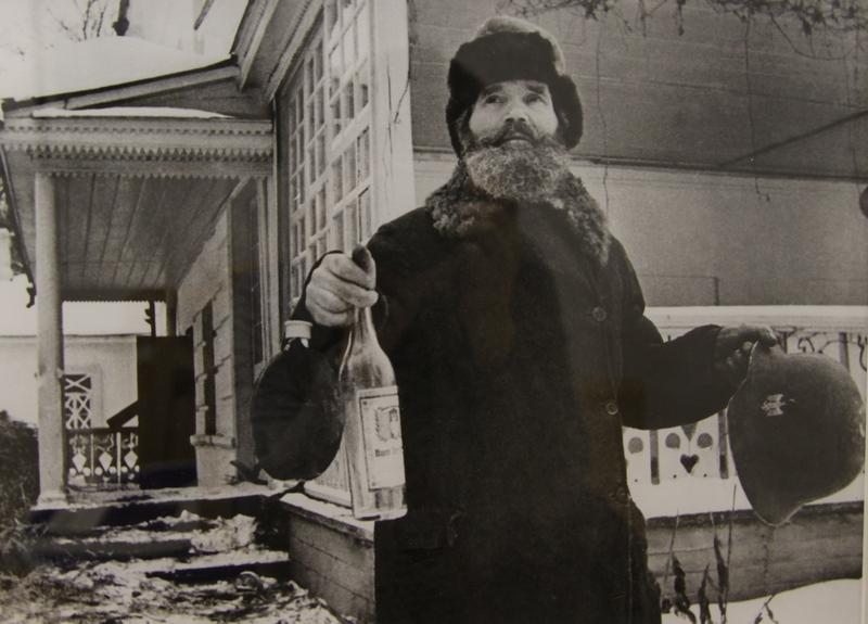 И.В. Егоров, бывший кучер Л.Н. Толстого, выносит из освобожденного дома писателя в Ясной Поляне бутылку шнапса и каску, оставшиеся после немецких солдат. 1941 г.